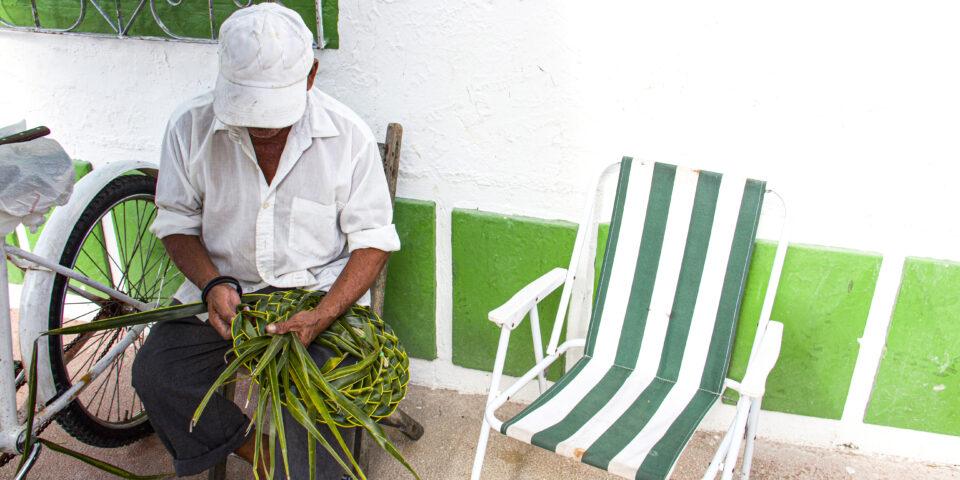 Imagen cozumel socieconómico, comercio local, creatividad cozumeleña, persona tejiendo sombrero de palma de coco