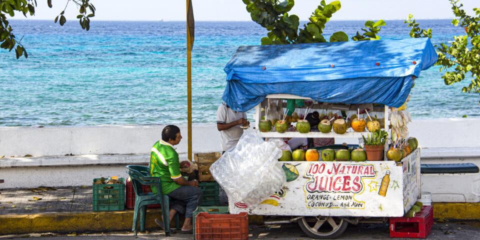 Imagen comercio cozumel, vendedor ambulante, mar caribe de fondo, mar azul cozumel